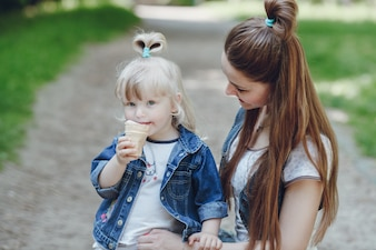 Mother looking at her daughter while eating an ice cream