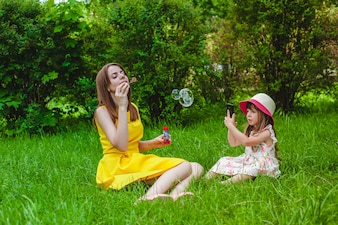 Mother making bubbles while her daughter takes pictures of her