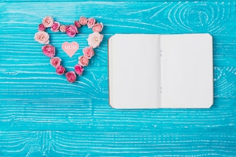 Mother's day composition with blank notebook and floral heart