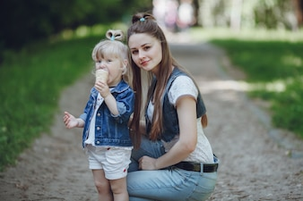 Mother squatting with her daughter while eating an ice cream with defocused background