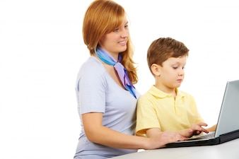 Mother teaching her child to use the laptop