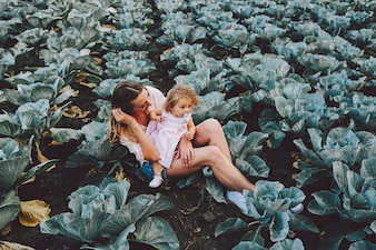 Mother with her daughter sitting on top of her in a field of cabbages