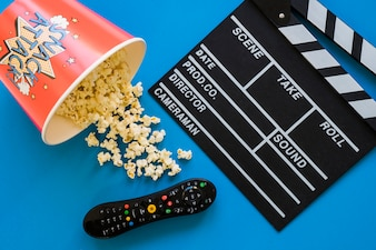 Movie concept with popcorn, clapperboard and remote control