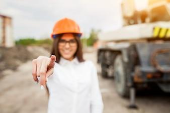 Mujer con un casco naranja mirando un plano