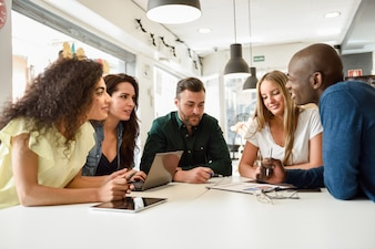 Multi-ethnic group of young people studying together on white de