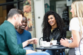 Multiracial group of four friends having a coffee together