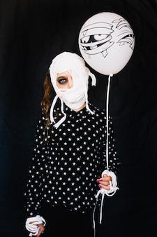 Mummy girl with bandages holding balloon