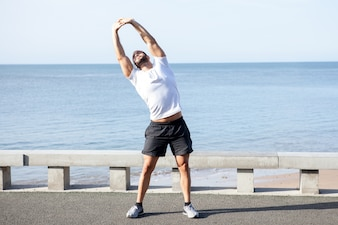 Muscular Man Doing Side Bend Exercise Outdoors