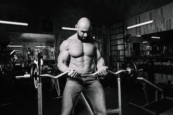 Muscular man holding heavy barbell