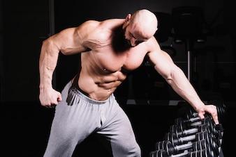 Muscular man leaning on dumbbell rack