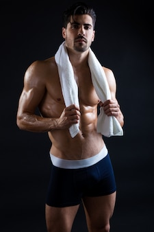 Muscular man posing with towel