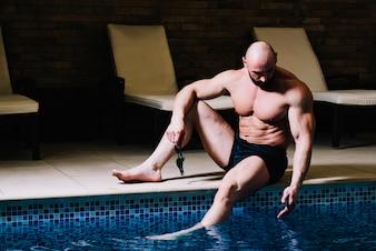Muscular man touching water
