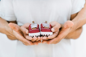 Newborn concept with gay couple holding shoes