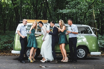 Newlyweds and guests on road in woods