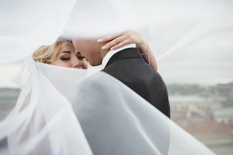Newlyweds covered by the veil of the bride