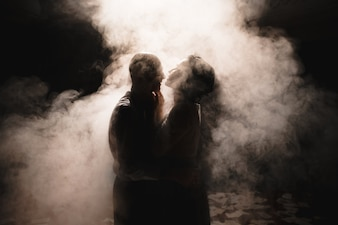 Newlyweds dancing among smoke