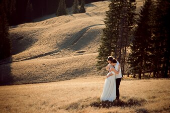 Newlyweds embraced in a field with pines
