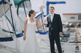 Newlyweds holding hands at the seaport