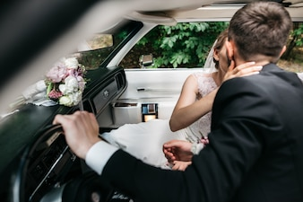 Newlyweds kiss inside a retro Cadillac