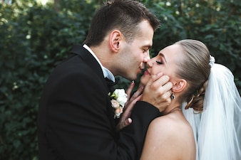 Newlyweds kissing in forest