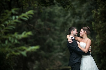 Newlyweds looking into their eyes with a forest in the background