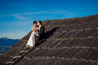 Newlyweds sitting on a roof