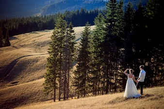 Newlyweds walking through a field with pines