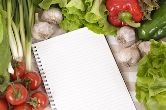 Notebook surrounded by vegetables