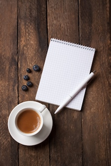 Notebook with a pen next to a cup of coffee