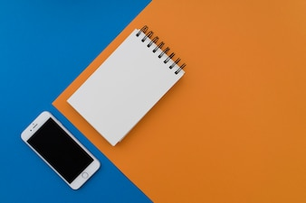 Notepad and smartphone on blue and orange background