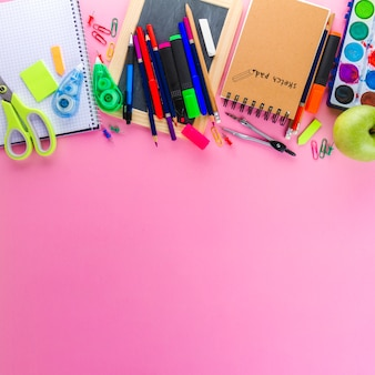 Notepads and pencils on pink