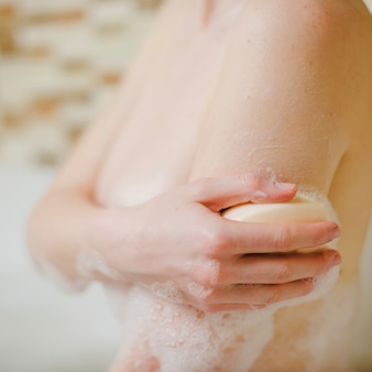 Nude woman soaping body