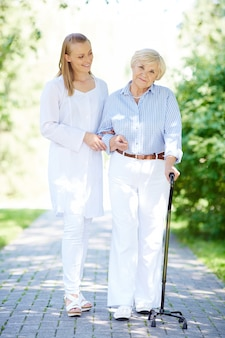 Nurse helping senior woman with walking stick