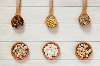 Nuts and seeds in spoons and bowls