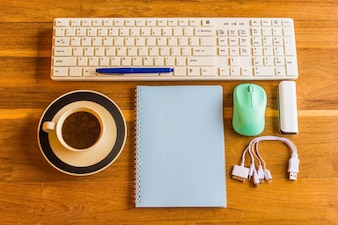 Office wooden table with notepad,Pen, keyboard,mouse,Phone charger and coffee cup. top view