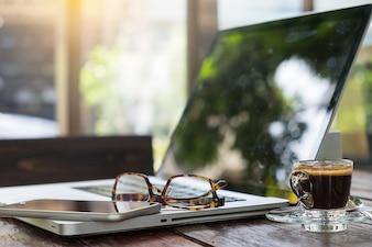 ラップトップと木製テーブル上の眼鏡を備えたオフィスの職場