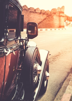 Old classic car parked on street in urban - vintage filter effect style