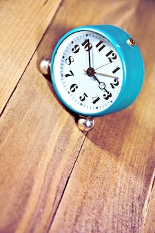 Old clock on the wooden background.