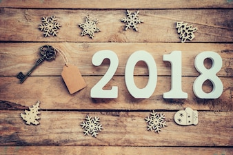Old key with tag and wooden numbers forming the number 2018, For the new year 2018 on a rustic wooden background.