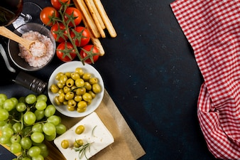 Olives, tomatoes and grapes on dark surface