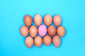 One preserved egg on blue background with chicken egg around.