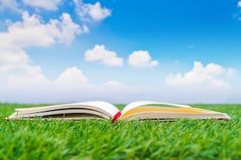 芝生の上でオープンノートブック