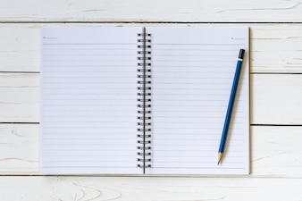 Open notebook with blank pages and pencil on wood table
