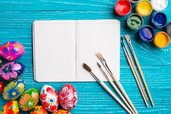 Open notebook with easter eggs and paint brushes