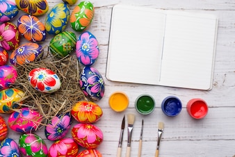 Open notebook with paint jars and easter eggs