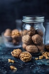 Open walnut with a galss jar background