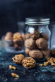 Open walnut with a galss jar background