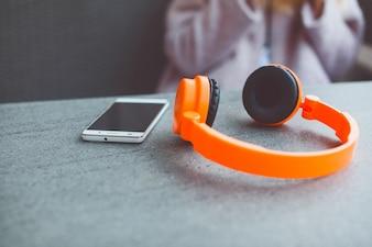 Orange headphones next to a smartphone