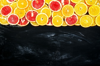 Oranges cut in slices on a black slate