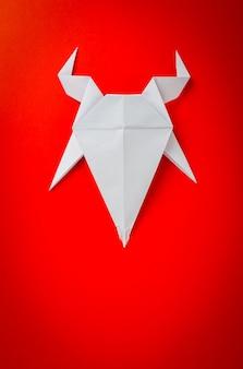 赤い背景上の折り紙紙ヤギ。ヤギ2015年の新年。